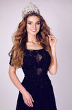 Gorgeous young woman with dark hair in luxurious dress with precious crown. Fashion studio photo of gorgeous young woman with dark hair in luxurious dress with Stock Photo