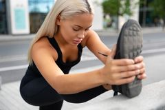 Gorgeous young Woman Doing Stretching Exercise At Sidewalk In City stock photography