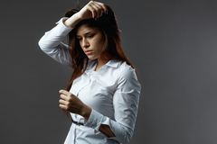 Gorgeous young woman dressed in white shirt with black belt stand on the dark gray background in the studio stock photos