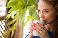 Gorgeous young woman drinking coffe in a coffee shop Royalty Free Stock Image