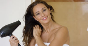 Gorgeous young woman drying her long hair Royalty Free Stock Image