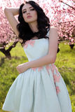 Gorgeous young woman in elegant dress posing in garden with blos Royalty Free Stock Image