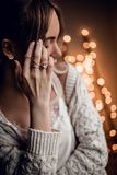 Gorgeous young woman with hand on golden bokeh lights background Royalty Free Stock Images