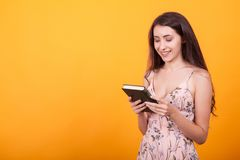 Gorgeous young woman holdin a book in studio over yellow background stock photos