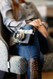 Gorgeous young woman holding camera in her hand. Woman sitting on a chair holding camera on her hand Stock Photography