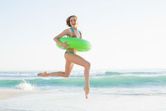 Gorgeous young woman holding a rubber ring while jumping on beach Stock Photography