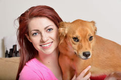 Gorgeous young woman at home with her dog Royalty Free Stock Photos