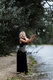 Gorgeous young woman in long black dress on beach royalty free stock photos