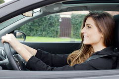 Gorgeous young woman with long hair sitting in car driving smiling happy Royalty Free Stock Photography