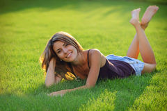 Gorgeous young woman lying down on grass Stock Photos
