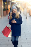 Gorgeous young woman out Christmas shopping. In a knitted winter cap smiling happily as she glances behind her while walking in an urban street Royalty Free Stock Photo
