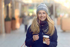 Gorgeous young woman out Christmas shopping. In a knitted winter cap smiling happily as she glances behind her while walking in an urban street Royalty Free Stock Image