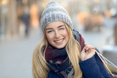 Gorgeous young woman out Christmas shopping. In a knitted winter cap smiling happily as she glances behind her while walking in an urban street Royalty Free Stock Photos