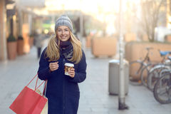 Gorgeous young woman out Christmas shopping. In a knitted winter cap smiling happily as she glances behind her while walking in an urban street Stock Image