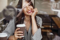 Gorgeous young woman with perfect white smile sitting in cafe wi royalty free stock images