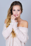 Gorgeous young woman in pink knitted sexy sweater with her shoulders open Stock Photos