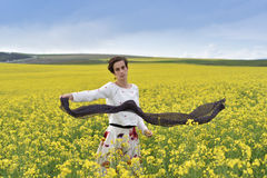 Gorgeous young woman playing with scarf in a canola field Royalty Free Stock Photos
