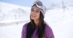 Gorgeous young woman posing in winter snow. Gorgeous young woman wearing goggles on her forehead posing in winter snow smiling happily at the camera  with copy Stock Photo