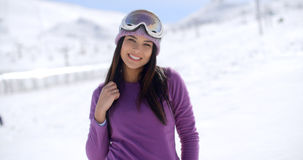 Gorgeous young woman posing in winter snow. Gorgeous young woman wearing goggles on her forehead posing in winter snow smiling happily at the camera  with copy Royalty Free Stock Photography