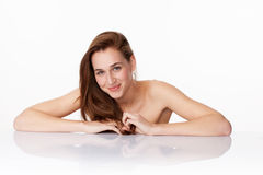 Gorgeous young woman relaxing for soothing spa treatment. Haircare and wellbeing concept - happy 20s woman with long brown hair smiling leaning on clear white Stock Photo