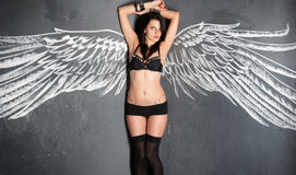 Gorgeous young woman in sexy black lingerie near wall with wing Royalty Free Stock Photography