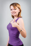 Gorgeous young woman showing big thumbs up. On the gray background stock photos