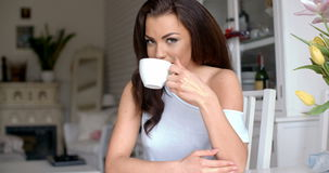 Gorgeous young woman sitting drinking coffee stock footage