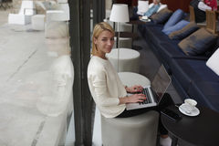Gorgeous young woman sitting with open laptop computer in modern coffee shop or hotel interior Stock Image