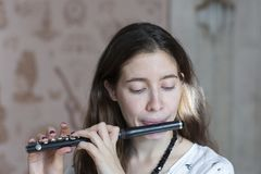 A gorgeous young woman sitting and playing the flute piccolo royalty free stock photography