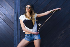 Gorgeous young woman with skate board on wooden door background Royalty Free Stock Images