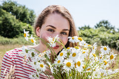 Gorgeous young woman smiling with camomile flowers for natural beauty Stock Photos