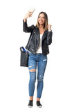 Gorgeous young woman in street style clothes taking selfie with mobile phone Stock Photos