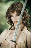 Gorgeous young woman holding a sword in the park Stock Images