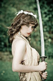 Gorgeous young woman holding a sword in the park Royalty Free Stock Photo