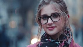 Gorgeous young woman in a stylish look and light makeup standing in the city-center, charmingly looking towards the stock footage