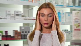 Gorgeous young woman suffering from headache at the drugstore. Woman rubbing her temples, having terrible migraine, shopping for medications at pharmacy stock footage