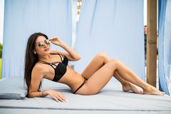 Gorgeous young woman in sunglasses lying in chaise-lounge by swimming pool. Gorgeous young woman lying in chaise-lounge by swimming pool stock images