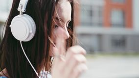 Gorgeous young woman in a trendy look, uses her phone, turns on the music, listens to the music with white headphones. Closes her eyes with joy, sings, moving stock video footage