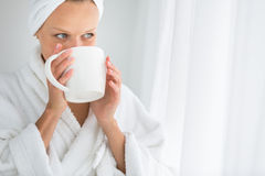 Gorgeous young woman wearing a bathrobe and enjoying a mug Stock Image