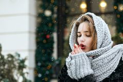 Gorgeous young woman wearing grey scarf warm her hands at the street. Space for text. Gorgeous brunette woman wearing grey scarf warm her hands at the street royalty free stock image