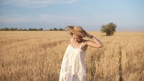 Gorgeous young woman in white dress runnung in the wheat field. Smiling, happy female running and holds her straw hat on stock footage