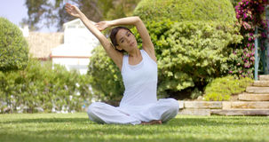 Gorgeous young woman in white sitting on lawn Stock Photography