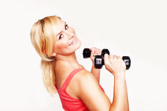 Gorgeous young woman working out. With hand weights to keep her slim figure shapely Royalty Free Stock Images