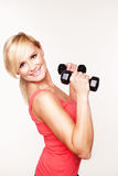 Gorgeous young woman working out. With hand weights to keep her slim figure shapely Stock Photography