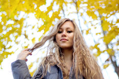 Gorgeous young woman on yellow autumn leaves background Stock Photo