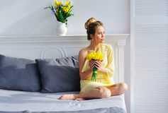 Gorgeous young woman with yellow tulips Royalty Free Stock Photos