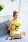 Gorgeous young woman with yellow tulips Stock Photos