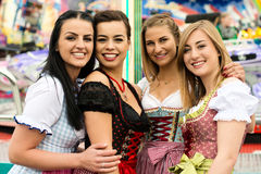 4 gorgeous young women at German funfair. Joyful young and attractive women at German funfair Oktoberfest with traditional dirndl dresses and joyride in the royalty free stock photography