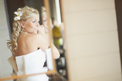 Gorgerous bride standing in front of mirror and fixing her hair Royalty Free Stock Photo