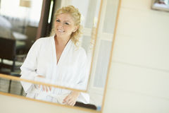Gorgerous bride standing in front of mirror and fixing her hair Royalty Free Stock Photography